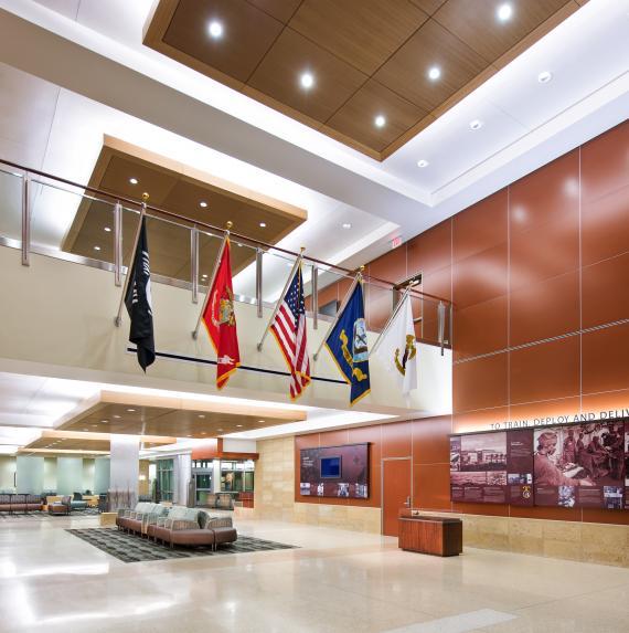 大厅天花板上装有吸音嵌板减少噪声。沙发周围的地毯显得温暖,也突出了空间感。大厅后部是模拟水的玻璃板。四处可见海军和海军陆战队的痕迹,比如那一面彭德尔顿营历史墙。.jpg
